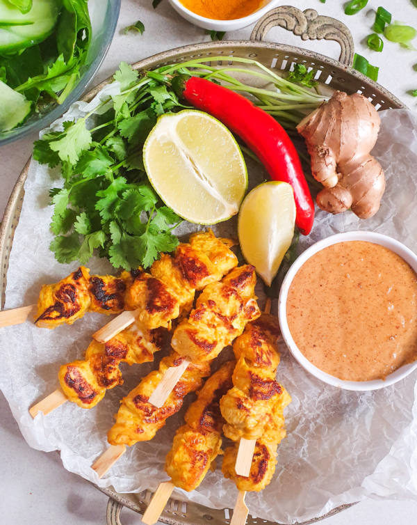 An image of a rustic tin platter with yellow satay chicken skewers, a red chilli, corriander, ginger and a lime. Paired with a dipping sauce