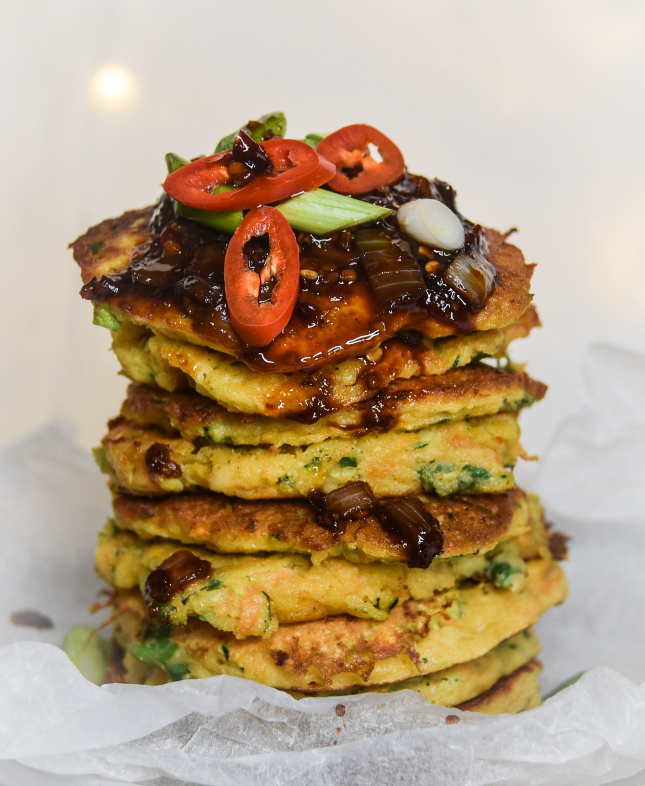 Picture of a stack of vegetable fritters with chilli jam and chillis on top