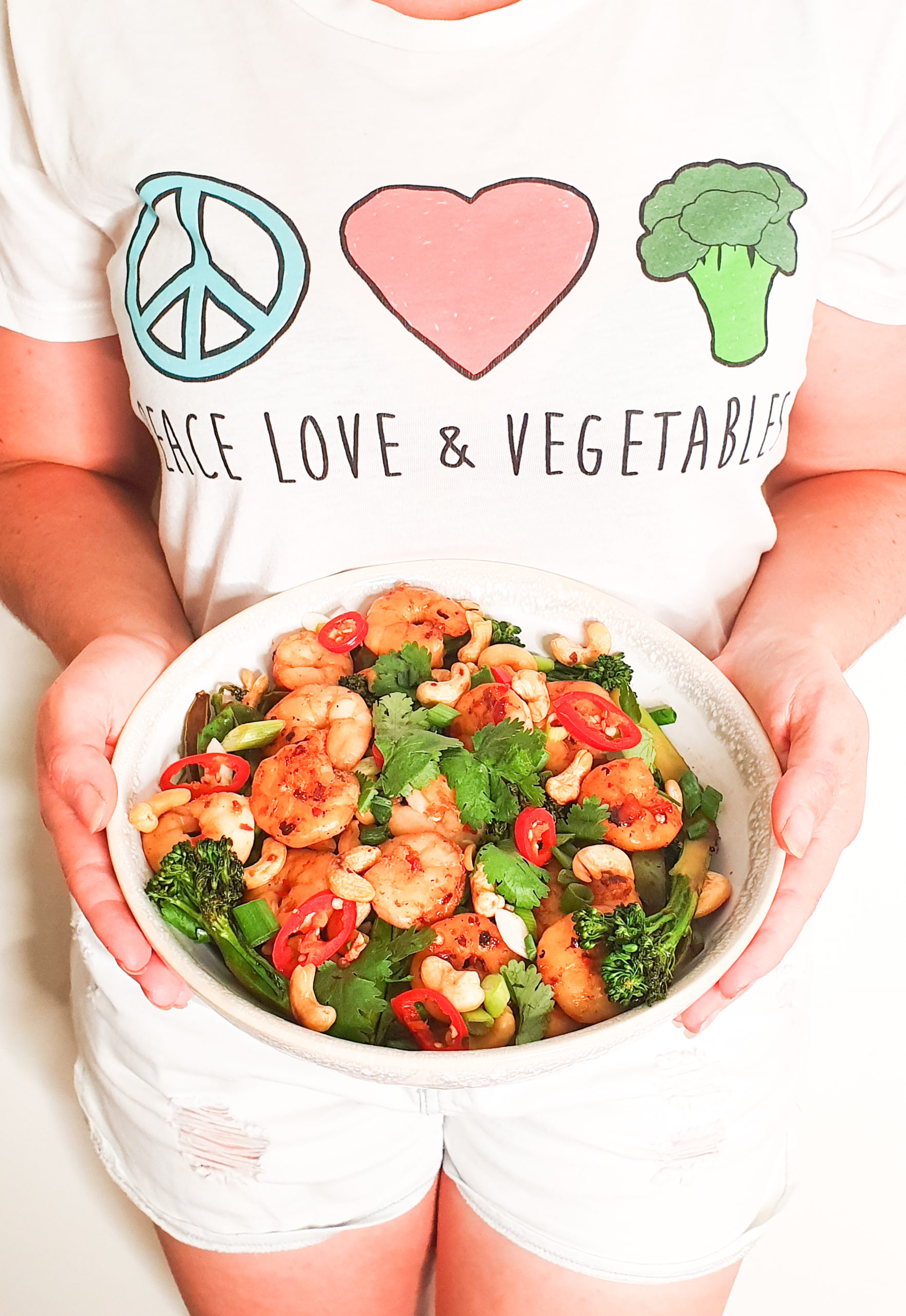 A picture of a person holding a bowl of cooked prawns and broccoli, a prawn and broccoli stir fry