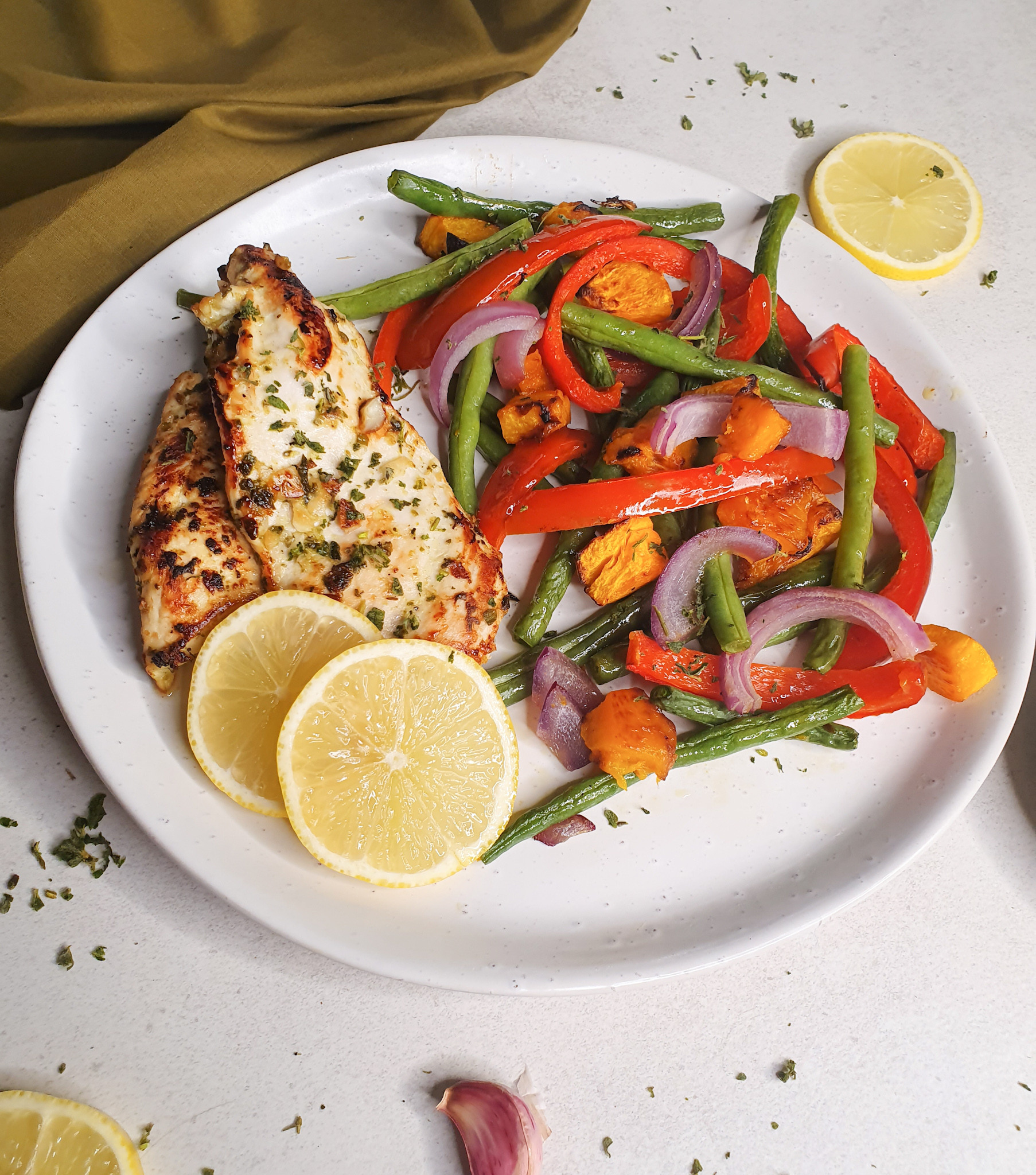 A Plate with grilled chicken and lemon slices with a side of beans, capsicum,onions and pumpkin