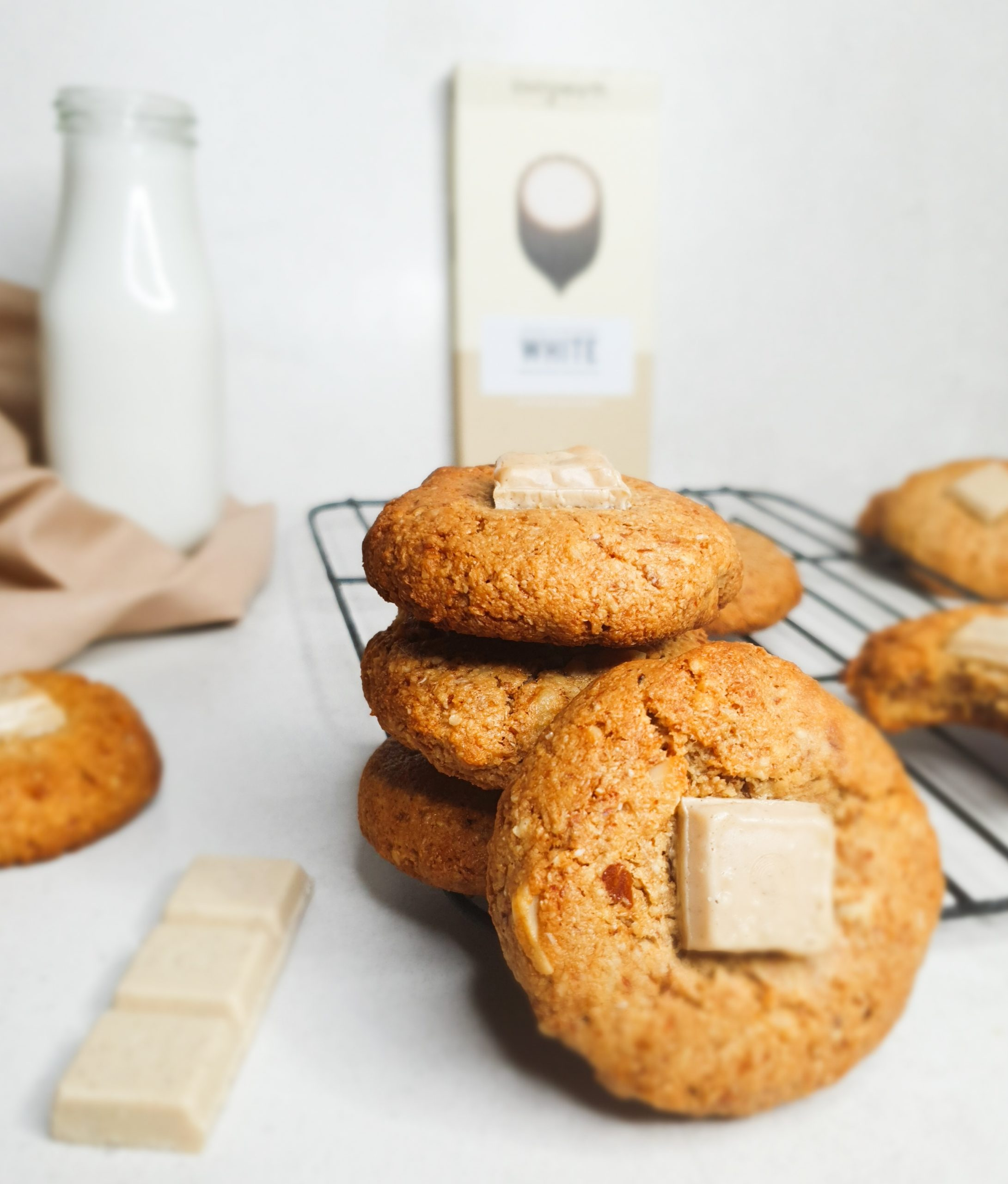 A Picture of Cookies stacked on a colling rack, with a bottle of milk and a block of chocolate in the background